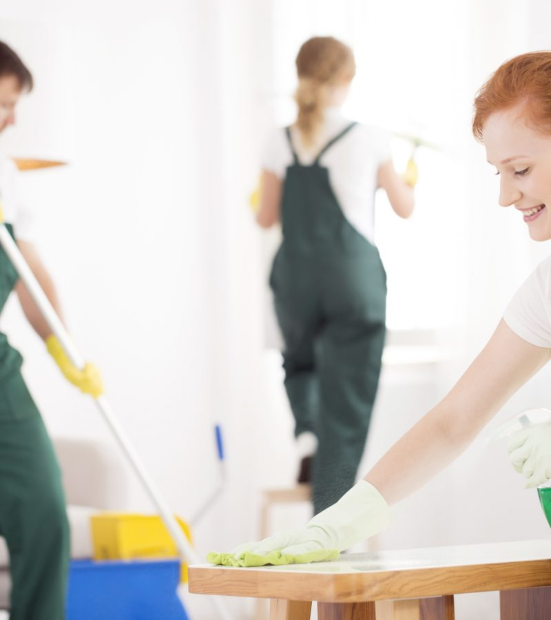 Cleaning service during work. Woman wiping a table while a man is washing the floor and other lady is cleaning the window